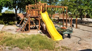 "UNCE Master Gardener Volunteer Liz Morrow turned this ""wooden backyard discovery equipment"" from something resembling ""a minor boot camp for tots"" into a ""beautiful new garden."" This is the before picture; keep reading to see the complete swing set makeover!"