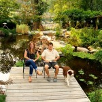 people sitting on deck in front on pond in garden