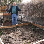garden bed with man standing holding rake