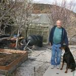 man with dog in backyard garden
